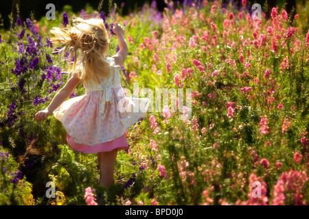 Giovane ragazza in esecuzione nel campo di fiori Foto Stock