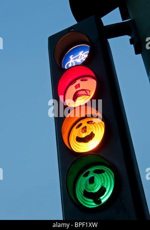 Facce disegnate sul ciclo di semafori al tramonto a Berlino Germania Foto Stock