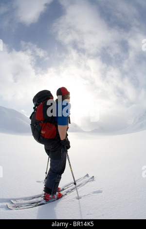 Backcountry rider attraversa il Glacier in tarda giornata cielo tempestoso. Foto Stock
