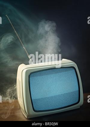 Tv rotta sul punto di esplodere. Studio shot, forma verticale, spazio di copia Foto Stock