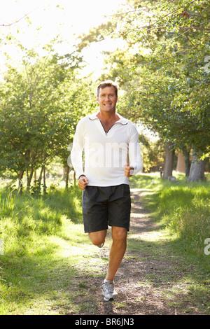 Uomo di mezza età a fare jogging nel parco Foto Stock