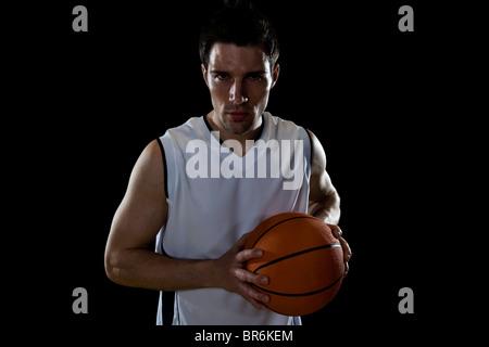 Un giocatore di basket la preparazione per il passaggio di una sfera, ritratto, studio shot Foto Stock