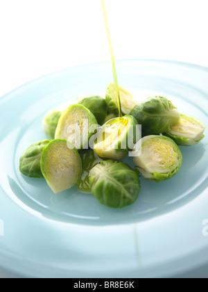 Condimento per insalata venga versato su cavoli di Bruxelles Foto Stock