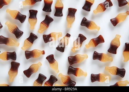 Bottiglia di cola caramelle sul retro bianco massa Foto Stock