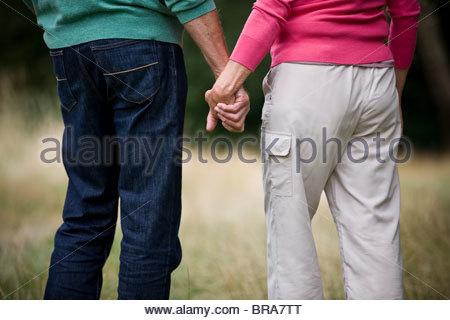 Una coppia senior Holding Hands, vista posteriore Foto Stock