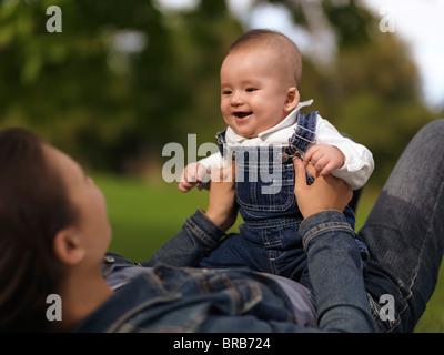 Madre giocando con una felice sorridente bambina di quattro mesi boy nella natura Foto Stock