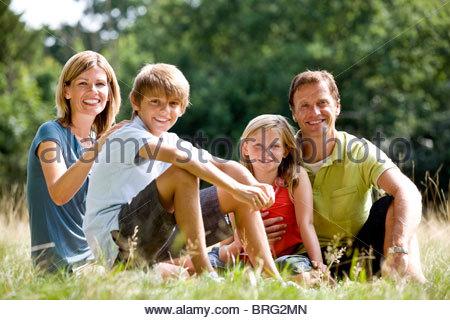 Una famiglia seduti insieme sull'erba Foto Stock