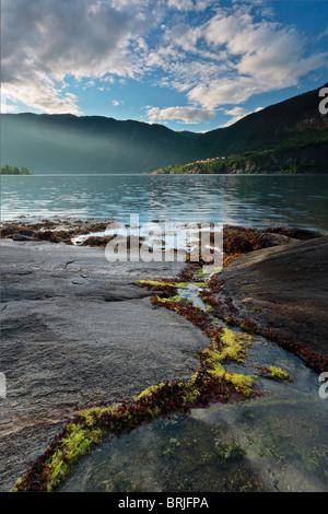 Raggi di sole rompere attraverso le nuvole e illuminare la sponda opposta del Sognefjord in Norvegia Foto Stock