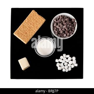 Ingredienti per s'more tartufo candy su una piastra nera tra cui graham crackers, scaglie di cioccolato e mini marshmallows Foto Stock