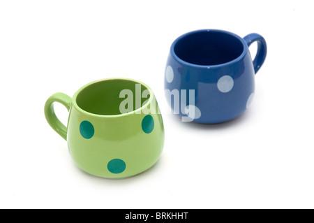 Il verde e il blu in ceramica vuoto tazze da caffè su uno sfondo bianco con ombra morbida Foto Stock