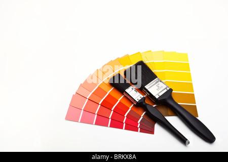 Pennelli per dipingere con rosso, giallo e arancione e marrone i campioni di colore Foto Stock