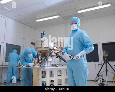 Lavoratore di sesso femminile che la costruzione di una parabola satellitare Foto Stock