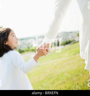Ragazza giovane azienda madre la mano e camminare nel campo Foto Stock