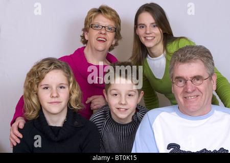 Mescolate unità familiare sorridente e guardare fotocamera contro uno sfondo bianco SerieCVS217053 2 Foto Stock