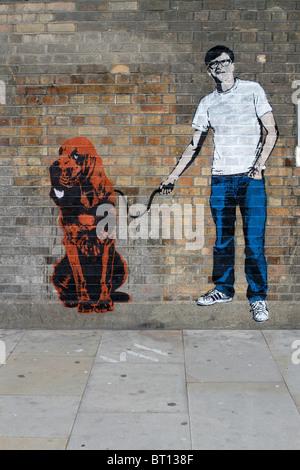 Uomo con cane stencil graffiti banksy stile, shoreditch Londra Foto Stock