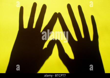 Due ombre a mano toccare su un brillante sfondo giallo Foto Stock