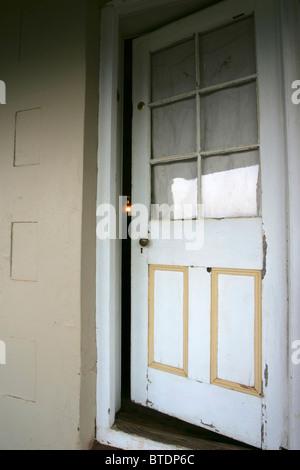 Un vecchio in legno bianco a sinistra della porta socchiusa con la debole luce proveniente da una lampada di paraffina Foto Stock
