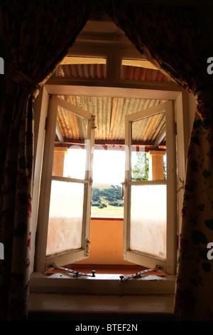 Vista dall'interno di un casale rustico attraverso una finestra aperta Foto Stock