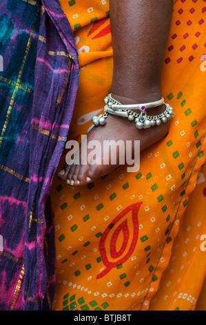 Bambini indiani piedi nudi contro le madri vestiti colorati. India Foto Stock