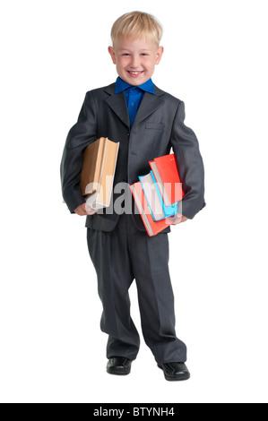 Giovani schoolboy azienda libri pesanti sotto le braccia Foto Stock