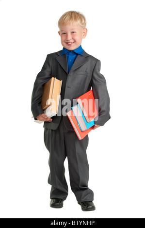 Giovani sorridente schoolboy azienda libri pesanti nelle sue braccia Foto Stock