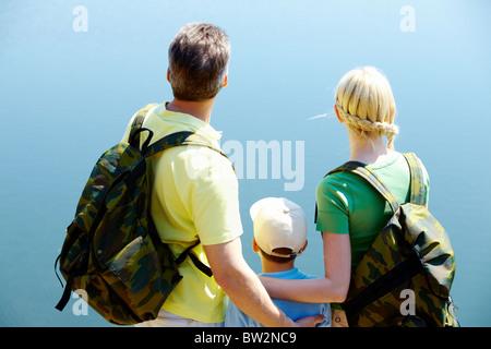 Vista posteriore della famiglia felice su sfondo blu Foto Stock