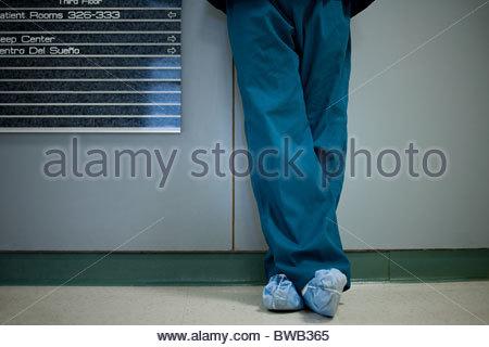 Chirurgo ospedaliero indossare protezioni per calzatura, sezione bassa Foto Stock