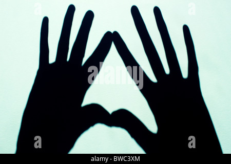 Due ombre a mano su fondo azzurro Foto Stock
