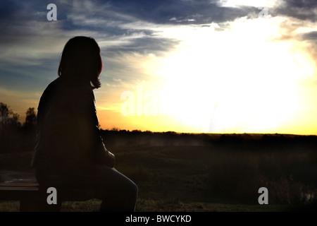Vista posteriore di una donna seduta a guardare verso un tramonto Foto Stock