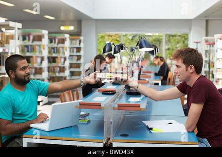 Due studenti del college seduto in biblioteca con computer portatile e la condivisione di libro. Sagoma orizzontale, vista laterale, spazio di copia
