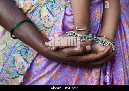 Bambini indiani piedi sulle madri le mani contro vestiti colorati. Andhra Pradesh, India Foto Stock