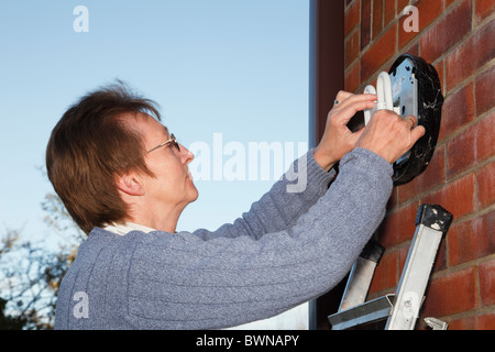 Il Regno Unito, l'Europa. Donna matura su una scala del montaggio di un risparmio energetico CFL a 2 pin della lampadina in una luce esterna
