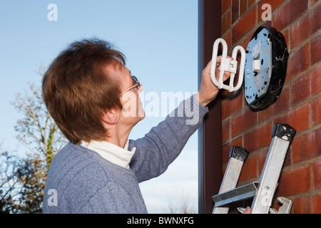 Il Regno Unito, l'Europa. Donna matura del montaggio di un risparmio energetico CFL a 2 pin della lampadina in una luce esterna
