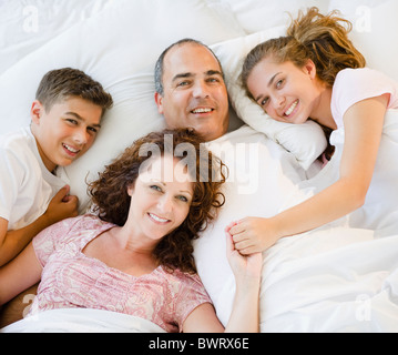 Sorridente famiglia ispanica che stabilisce nel letto insieme Foto Stock