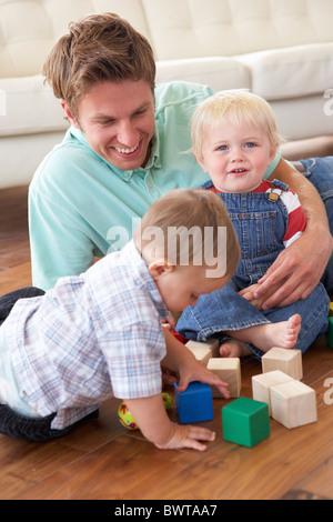 Padre e figli giocare con i blocchi colorati a casa Foto Stock