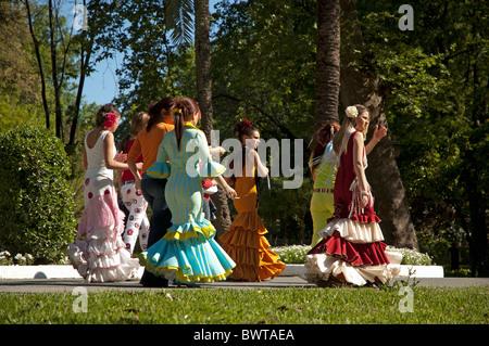 Le donne in abito di flamenco a piedi attraverso il Parco Maria Luisa verso il Siviglia Fiera di Primavera, Siviglia, Foto Stock