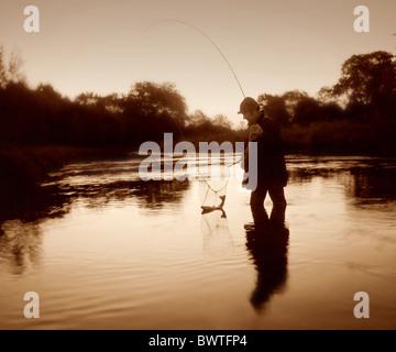 L'uomo la pesca nel flusso Foto Stock