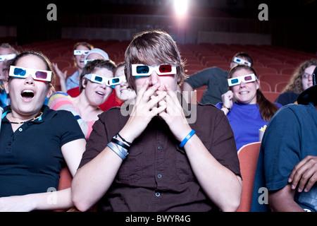 Amici guardando film in teatro indossando occhiali 3D Foto Stock
