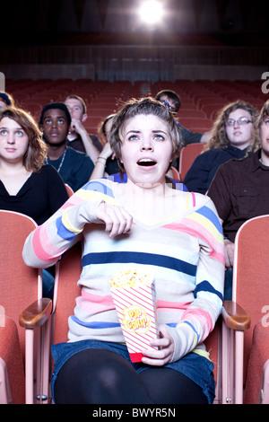 Sorpreso donna caucasica mangiare popcorn in movie theater Foto Stock