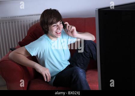 Giovane maschio in possesso di un telefono cellulare sorridente e guardare la tv Foto Stock