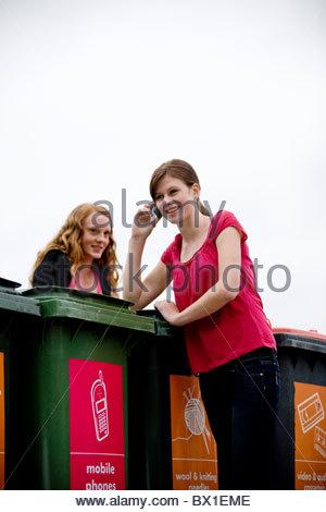 Una ragazza adolescente utilizzando un telefono cellulare in un centro di riciclaggio Foto Stock