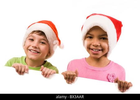 Foto di felice amici in santa caps sorridente in telecamera Foto Stock