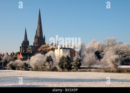 Lichfield Cathedral spires visto fro Stowe campi sotto la neve con trasformata per forte gradiente la brina su alberi e in inverno la neve sulla terra sotto il cielo blu Foto Stock