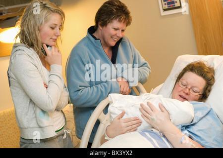 Una madre detiene il suo neonato in ospedale come due visitatori femmina guarda su; miglio, Alberta, Canada Foto Stock