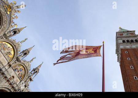 Il campanile e la Basilica di San Marco, Piazza San Marco, con bandiera veneziana, Venezia, Sito Patrimonio Mondiale Foto Stock