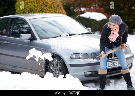 Donna scavo auto da neve Foto Stock