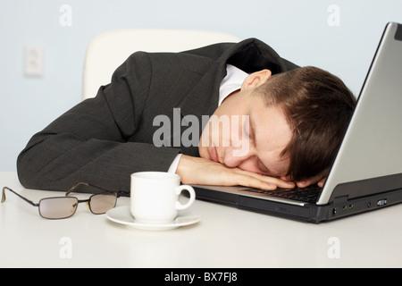 Un giovane imprenditore non abbastanza sonno e si è addormentato sul lavoro Foto Stock