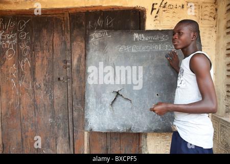 Un giovane uomo scrive su una lavagna di scuola in Masiaka, Sierra Leone, Africa occidentale. Foto Stock
