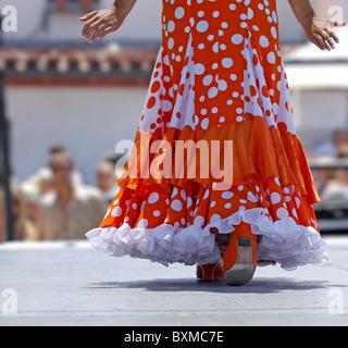 La ballerina di flamenco in un abito arancione camminando sul palco Foto Stock