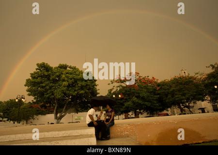 Un giovane si siede in una pubblica piazza sotto un arcobaleno usando un ombrello come piove in stato dello Yucatan, Foto Stock